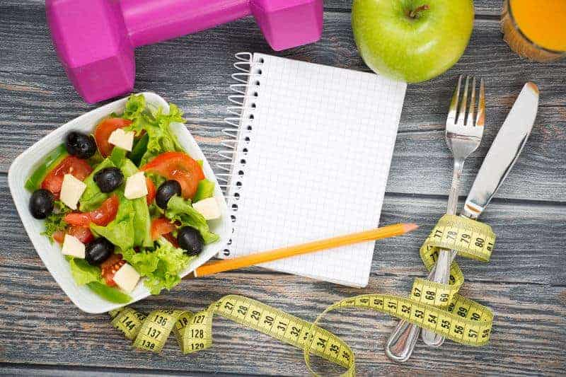 bowl of salad and notebook to track healthy eating