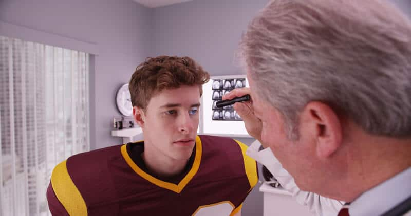 football player being examined by a doctor for a concussion