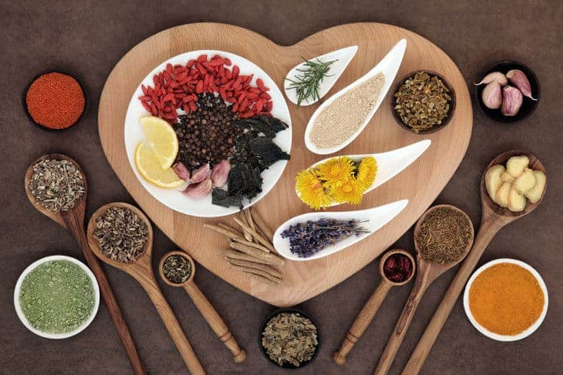 healthy nuts, grains, beans, and spices on a heart platter