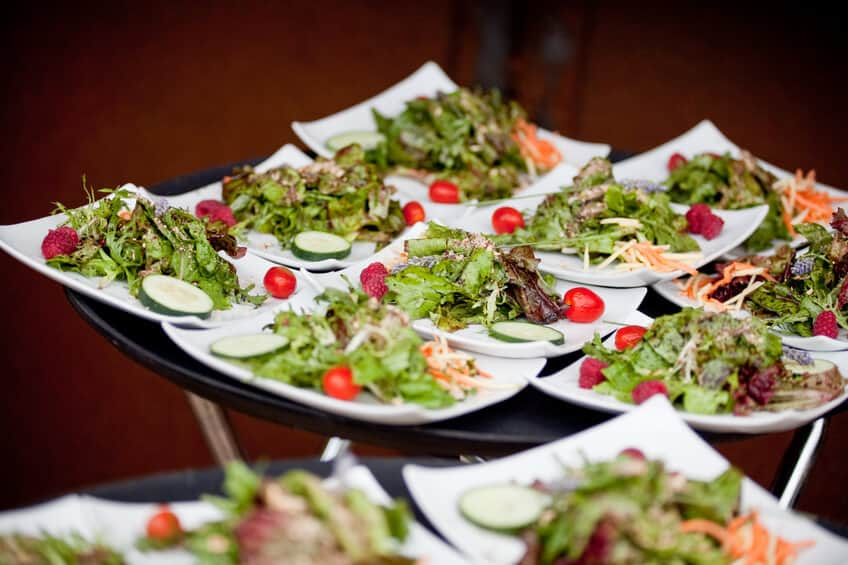 """A tray of plated fresh salad for wedding guests.  The salad has mixed greens, tomatoes, cucumbers, and raspberries."""
