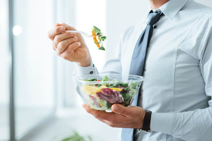 Businessman having a vegetables salad for lunch, healthy eating and lifestyle concept, unrecognizable person