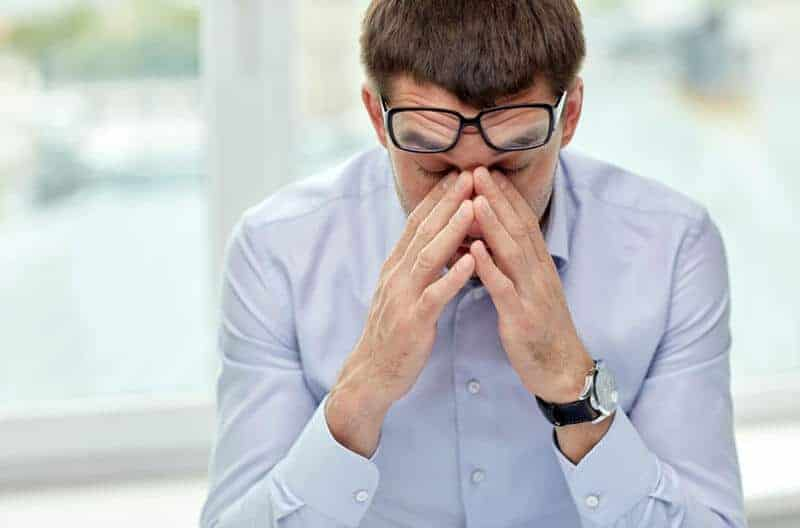 man wearing glasses stressed out working