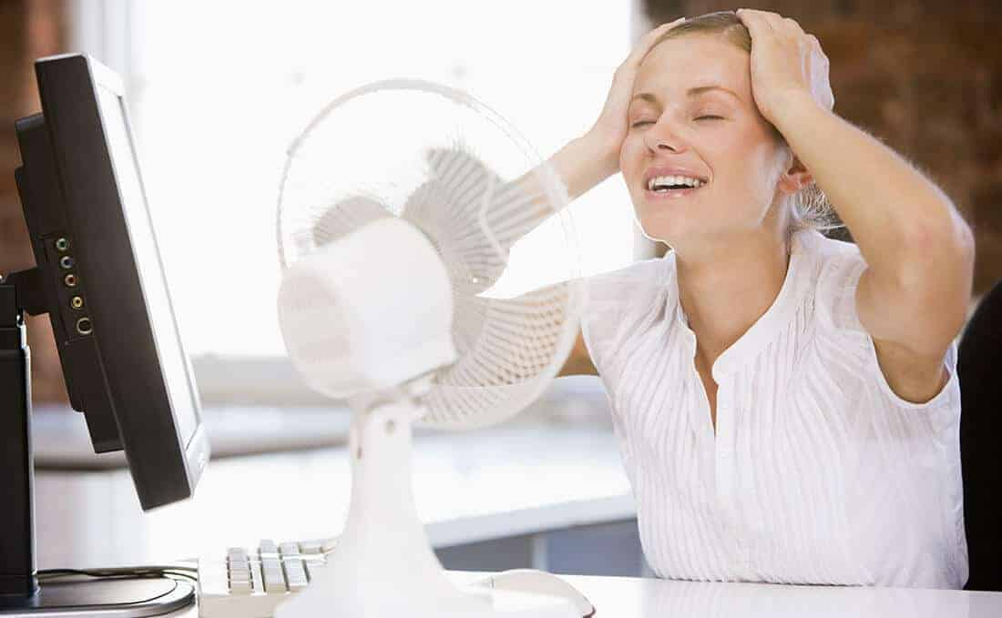 woman cool off with a fan during hot flashes
