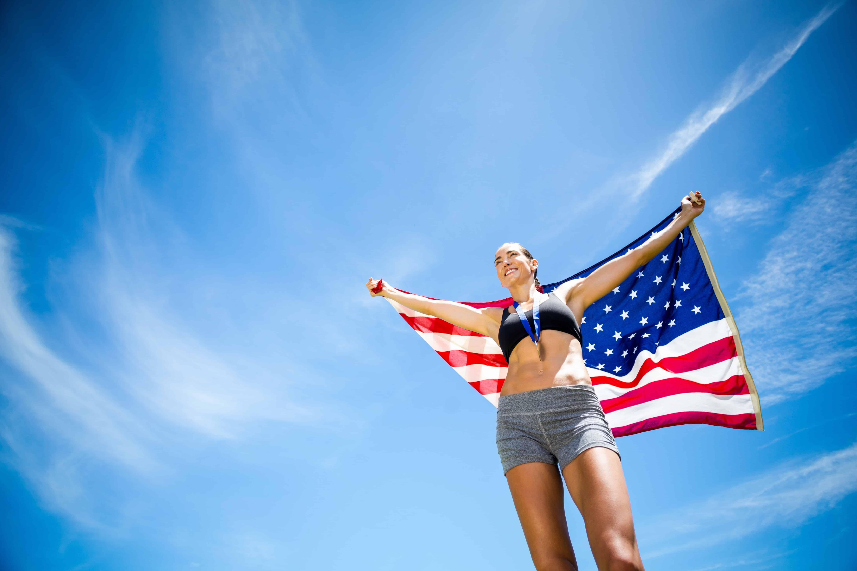 woman holding an American flag after winning a marathon