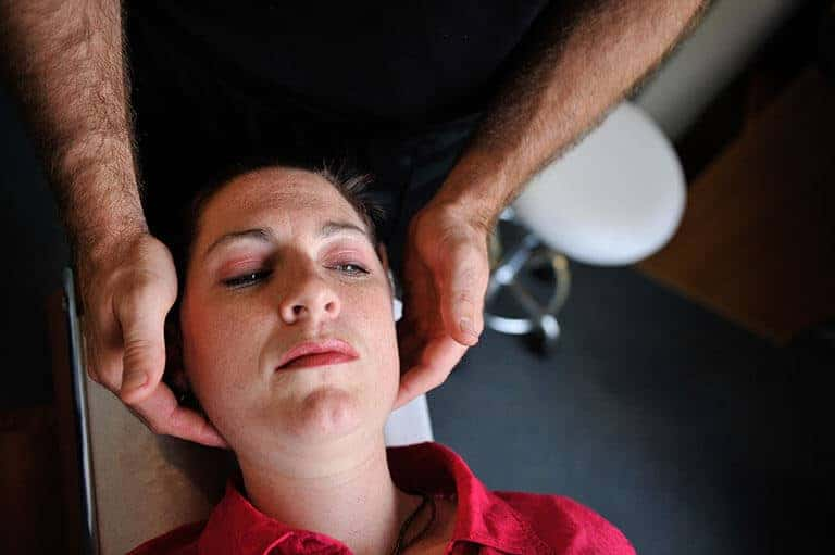 woman receiving physiotherapy treatment to her neck and head