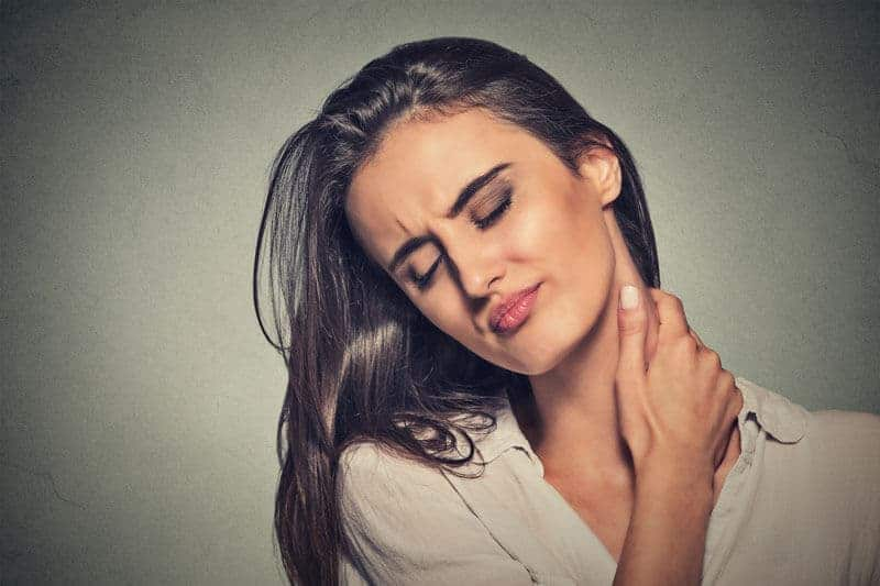 woman tilting her head with neck pain