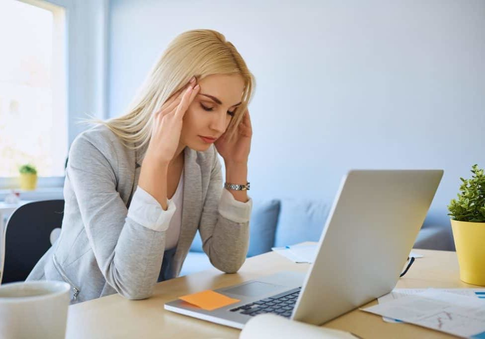woman with a headache at her computer