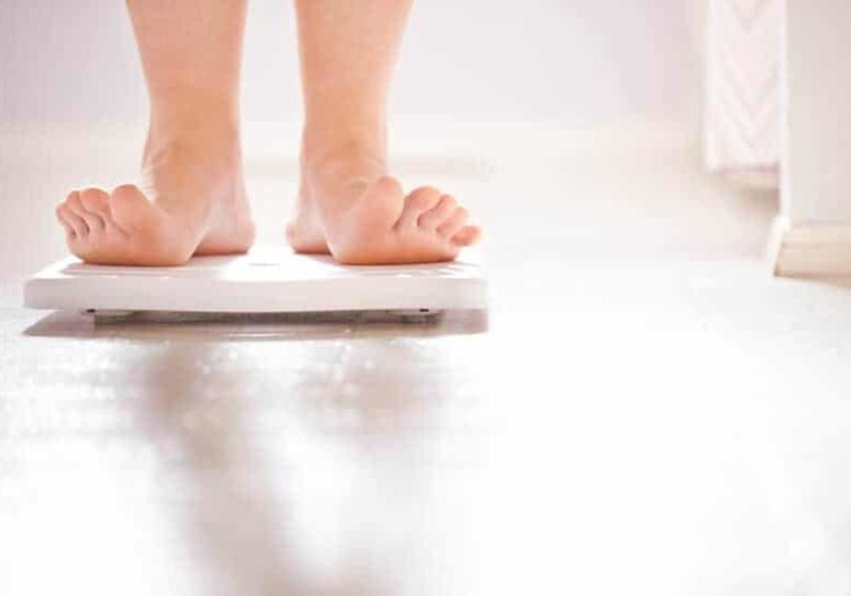 person weighing themselves on a bathroom scale