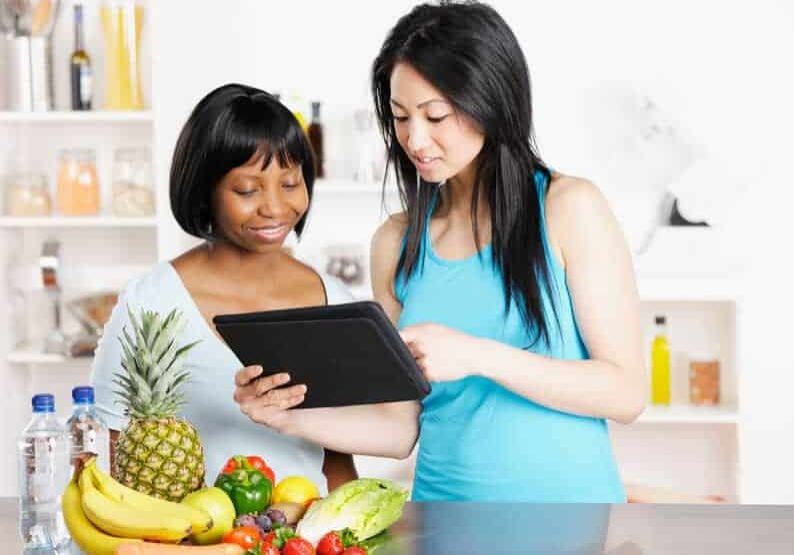 dietitian showing client a diet/ food plan on a digital tablet.