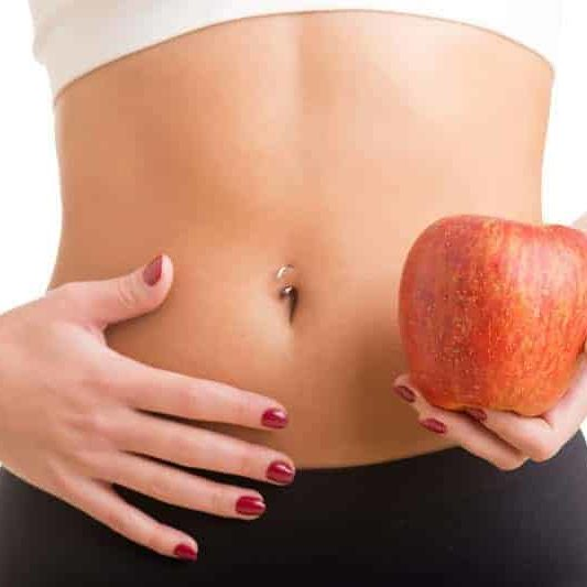 woman holding an apple with a healthy stomache